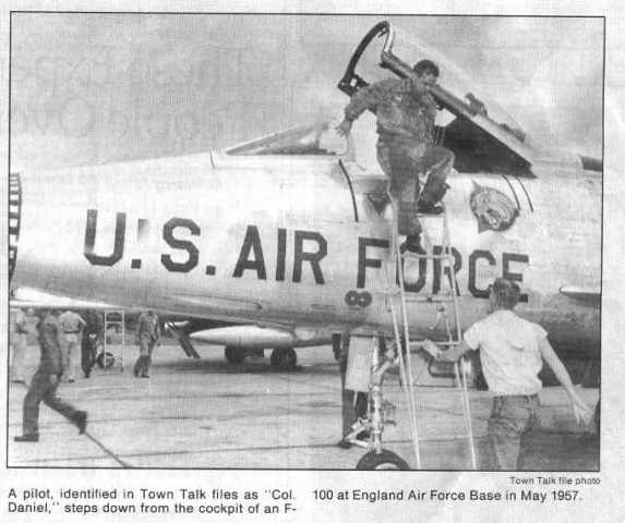 Newspaper account: A pilot identified at Colonel Daniel steps down from the cockpit of an F-100 at Eng at England Air Force Base in May of 1957